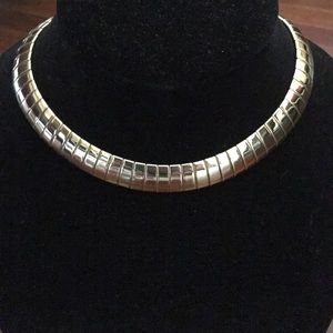 Gold tone choker style necklace.